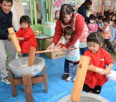 大人と一緒に餅つきに挑戦する子どもたち=佐賀市久保田町の久保田幼稚園くぼたれんげ保育園