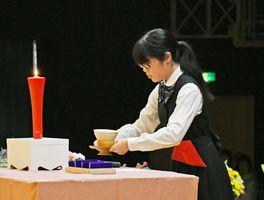 佐賀女子高茶道部の生徒が、校祖の中島ヤスさんにお茶をささげた=旭学園の体育館