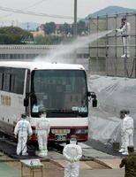 被ばくした想定で避難車両を流水で除染する自衛隊員=4日午後0時57分、多久市陸上競技場
