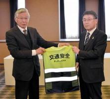 反射材が入った交通安全ベストを贈呈する大串本部長(右)と県交通安全協会の坂井邦夫会長=佐賀市のグランデはがくれ