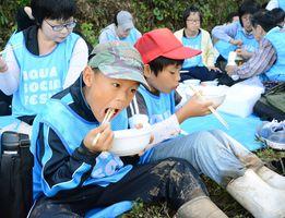 稲刈りの後、蕨野の棚田でとれた新米のおにぎりと豚汁を味わう参加者=唐津市相知町