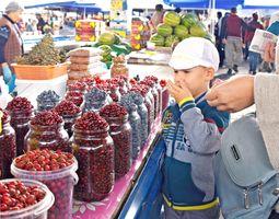 市場には新鮮な果物や野菜が積まれ、活気にあふれる。山盛りのベリーの瓶から、ひと粒つまんで味見してみる少年も=ハバロフスク