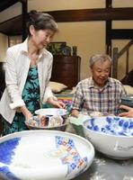 「器に恵まれているから料理が楽しい」と話す小池範江さん(左)。右は夫の正博さん=武雄市武雄町