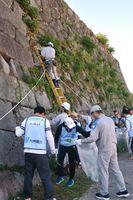 石垣の雑草をかまで除去する九電従業員ら=佐賀市の鯱の門周辺
