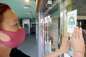 感染防止協力店を示す「虹ステッカー」を確認する田中さん=東京・三軒茶屋のサンタワーズA