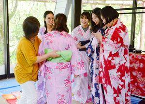 浴衣の着付けを体験する中国人留学生たち=佐賀市の徐福長寿館内