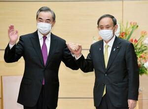 会談前、グータッチを交わす中国の王毅国務委員兼外相(左)と菅義偉首相=25日午後、首相官邸