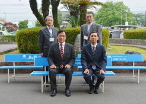 寄贈されたベンチに座る横尾俊彦市長(前列左)と和光の眞﨑久司社長(同右)=多久市役所