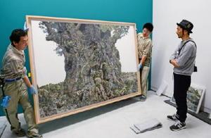 20日の開幕に向け、搬入された作品をチェックする池田学さん(右)=佐賀市の佐賀県立美術館