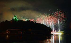 仕掛け花火「ナイアガラ」が海面を照らす=15日夜、唐津市の舞鶴橋から撮影