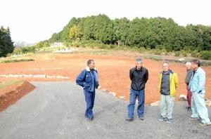 白岩地区に整備された果樹試験栽培場で新たな果樹栽培に向けて話し合う組合メンバー=杵島郡白石町
