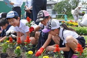花苗植えの作業を楽しみ、笑顔を見せる児童=佐賀市の金立公民館