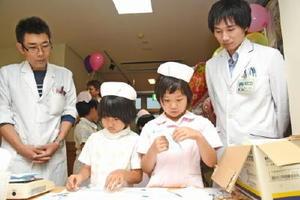 薬剤師の話を聞いて調合や薬の処方を行う子どもたち=鹿島市の志田病院