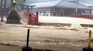 祐徳稲荷神社そばの浜川(赤い欄干の下)からあふれる濁流。門前商店街が浸水した=6日午後、鹿島市古枝(読者提供)