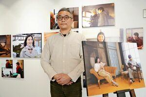 映画「越年 Lovers」のスチール写真を展示している富永茂樹さん=佐賀市のcosa