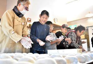手際よく餅を丸める三気の会の会員と子どもたち=佐賀市のひょうたん島公園