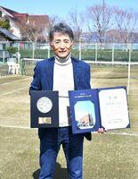 天然芝生コートの前で笑顔を見せる緒方周代表=佐賀市金立町のグラスコート佐賀テニスクラブ