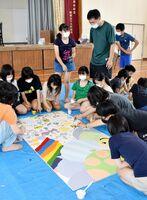壁板に絵を塗る6年生=伊万里市の立花小体育館