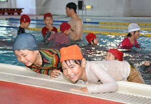 水に落ちたときの危険について学ぶ落水体験教室で、水で重くなった服を着たまま、プールサイドにはい上がろうとする鳳鳴乃里幼稚舎の園児たち=佐賀市のリョーユースポーツプラザ(25日付14面)