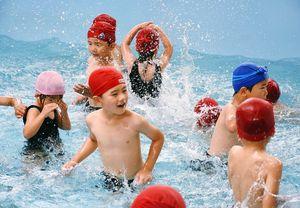 水の掛け合いを楽しむ年長の園児たち=佐賀市の認定こども園「嘉瀬こどもの森」