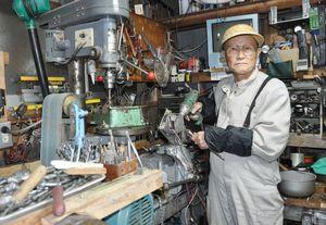 自宅の作業場で機械器具を使い修理する西村亘さん
