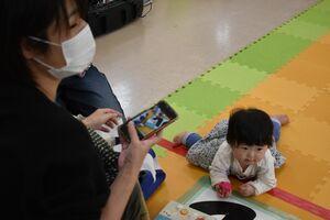 家族に見守られながらハイハイし、ゴールした乳幼児=佐賀市新栄東の総合住宅展示場イエス