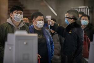 23日、中国・武漢から鉄道で北京に到着した旅客の熱を測る検査員(ゲッティ=共同)