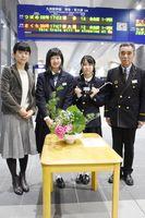 JR新鳥栖駅に飾られた生け花を前に、左から松隈教諭、上林さん、森野さん、澤田駅長