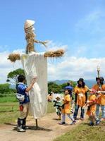 完成した身長3㍍の巨大かかしに驚く子どもたち=吉野ケ里歴史公園