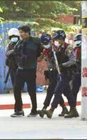 2月26日、ミャンマー治安当局に拘束されるフリージャーナリストの北角裕樹さん(左から2人目)=ヤンゴン(デモ参加者提供、共同)