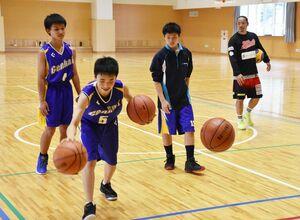 原慎也主将(右)の指導の下、複数のボールを使ってドリブルをする生徒たち=玄海町の玄海みらい学園
