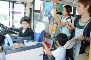 運転士の格好をした子どもを撮影する家族連れ=佐賀市の佐賀駅バスセンター