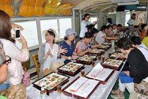 船内でエツづくしの弁当を広げる参加者ら