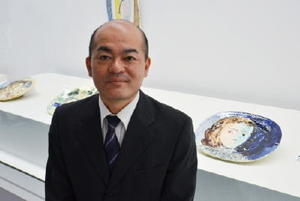 右後方にある「女の肖像の楕円皿」など、ピカソ作品の目の開き方や位置に着目した德安和博さん=佐賀市の県立美術館