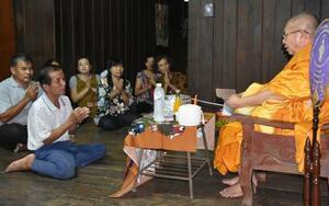 12日、北朝鮮に拉致されたとみられるタイ人女性アノーチャー・パンチョイさんの65歳の誕生日の寄進式で祈る親族ら=タイ北部チェンマイ(共同)