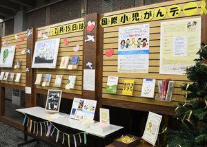 会場には小児がんに関する本や絵画が並ぶ=佐賀市の県立図書館