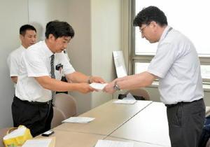 要請書を手渡す佐賀県私立学校教職員組合連合の米倉嘉康委員長(左)=県庁