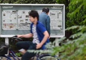 佐賀新聞社前の掲示板に張り出された紙面に見入る男性(奥)=佐賀市天神3丁目