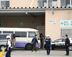 クマの侵入口になったとみられる、商業施設の搬入口付近を警戒する警察官=19日午後3時50分ごろ、石川県加賀市