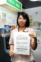 8月8日から始まるATM振り込み制限の張り紙を持つ職員=佐賀市神野東の佐賀東信用組合