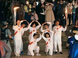 東大寺南大門近くで聖火ランナーたちとポーズをとる映画監督の河瀬直美さん(左端)=12日夜、奈良市