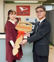 贈呈式で、畑島幸博社長(右)からキーを受け取る南里裕紀子さん=佐賀市嘉瀬町の佐賀ダイハツ販売本社