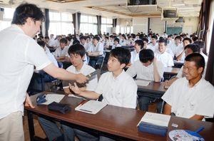 主権者教育アドバイザーを務めるネクスト・コネクションの越智大貴代表(左)が出した思考実験の問題に答える白石高3年の生徒ら=白石町の白石高