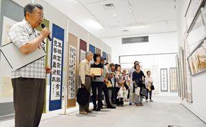 ギャラリートークで作品を解説する県書作家協会の福地秀鵬会長(左)=佐賀県立美術館