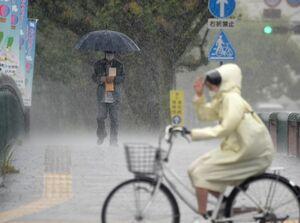 強い雨が降る中、傘やレインコートを着て行き交う人たち。佐賀県を含む九州北部地方は統計開始以降、2番目に早い梅雨入りとなった=15日午前、佐賀市内(撮影・鶴澤弘樹)