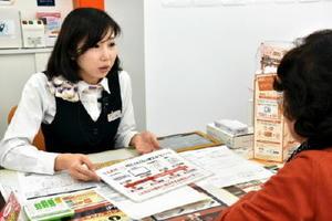 携帯電話の機種変更に来た客に自社の電気プランを説明するスタッフ=佐賀市のauショップ西佐賀
