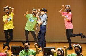 制服警察官の姿でニセ電話詐欺防止テーマソング「にゃんこパトロール」を披露したカノエラナさん(右から2人目)=佐賀市のメートプラザ佐賀