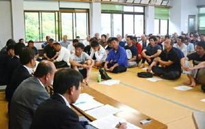 農水省の担当者(左)の説明を聞く漁業者たち=太良町の佐賀県有明海漁協大浦支所