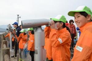 ラムサール条約の湿地登録を受け、新たに設置された望遠鏡。小学生たちが干潟や野鳥を観察している=佐賀県鹿島市の新籠海岸