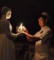 ナイチンゲール像から火をともす学生=佐賀市の県立総合看護学院